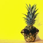 Pineapple wears sunglasses with yellow background