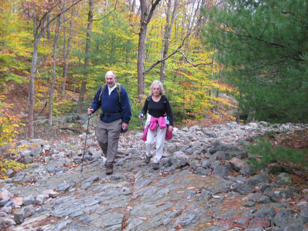 A man and woman walk a trail beside trees in autumn colors.