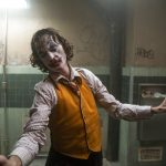 A man in clown makeup dances in a bathroom.